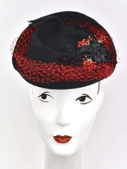 Black wool headpiece with red netting overlay, black velvet and ribbon