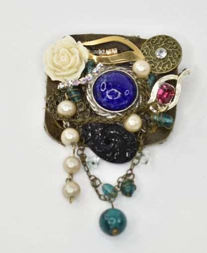 A Unique brooch with made in a mixed media style with a dominant black chain detail. Attaches with pin back One of a kind Materials vary from vintage and new components