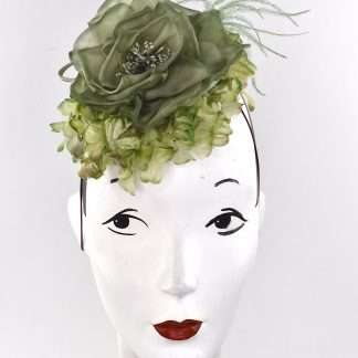 Spring it up in with this large silk flower adorned with vintage green flowers. Perfect for you ladies who do not want to stand out too much in the crowd. Will suit any patterned dress as well compliment most colors. Attaches with a hat elastic on a sinamay base.