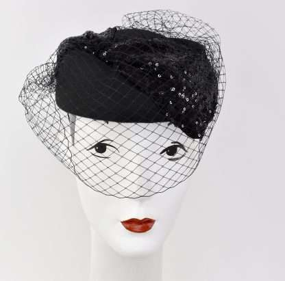 This lovely Jackie O inspired pillbox/stewardess styled hat is made of 100% black wool and detailed with black netting ! One of a kind ! Attaches with hat elastic. Looks fabulous on and you will be ready for the holidays in this one!